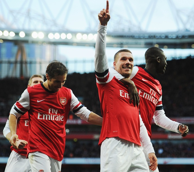 Lukas Podolski, left, of Arsenal celebrates with team mate Yaya Sanogo after scoring.