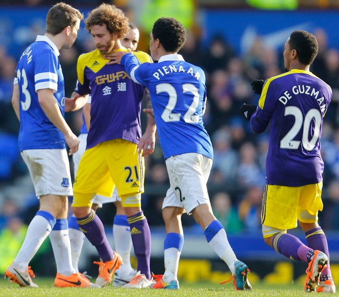 Steven Pienaar, centre, of Everton pushes Jose Canas of Swansea City in an altercation.