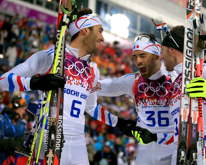 France's gold medalist Martin Fourcade (left) celebrates with brother Simon Fourcade (centre) at the finish area after the men's 12.5 km Pursuit at Laura Cross-country Ski & Biathlon Center during the Sochi Winter Olympics