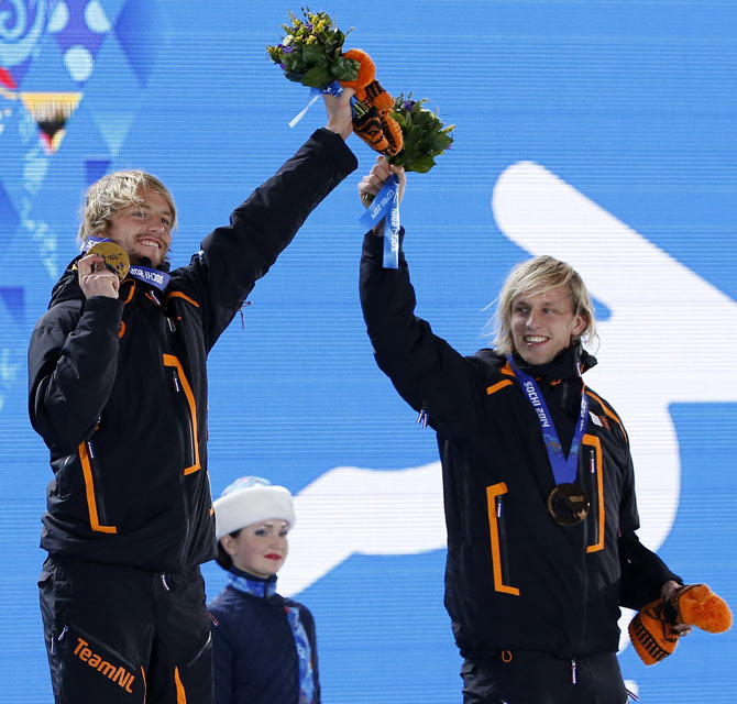 Gold medallist Michel Mulder of the Netherlands (left) celebrates with his brother and bronze medallist Ronald Mulder (right), during the victory ceremony for the men's speed skating 500m race at the 2014 Sochi Winter Olympics