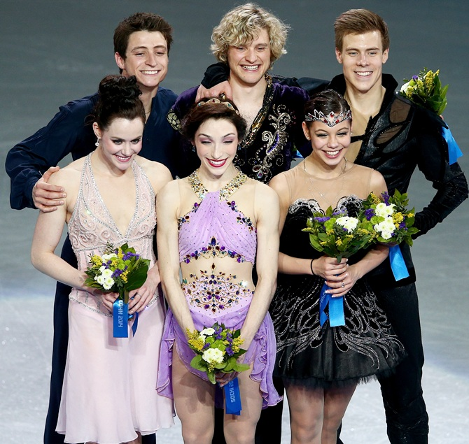 From left, Silver medalists Tessa Virtue and Scott Moir of Canada, gold medalists Meryl Davis and Charlie White of the United States, and bronze medalists Elena Ilinykh and Nikita Katsalapov of Russia celebrate on the podium during the flower ceremony for the Figure Skating Ice Dance.
