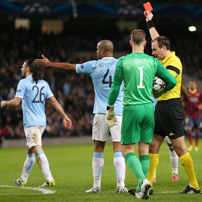Referee Jonas Eriksson shows a red card to Martin Demichelis of Manchester City.
