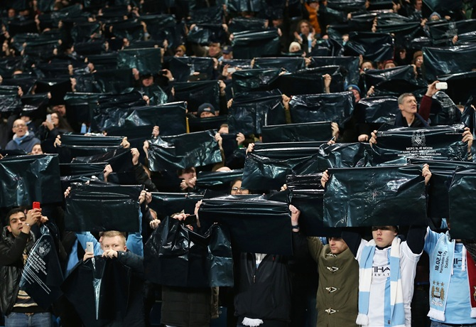 Manchester City fans hold up banners prior to the UEFA Champions League Round of 16 first leg match.