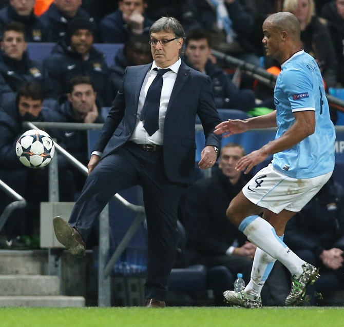 Barcelona Head Coach Gerardo Martino beats Vincent Kompany of Manchester City to the ball.