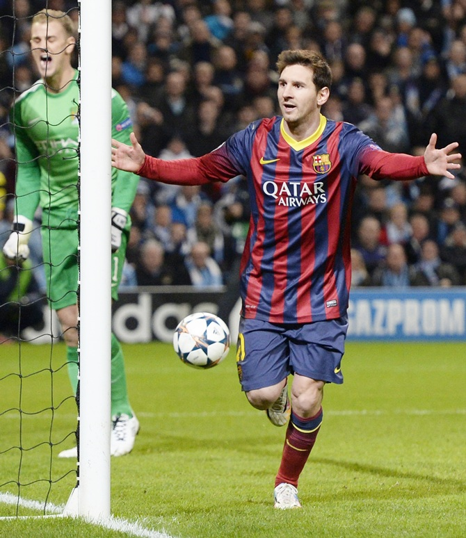 Barcelona's Lionel Messi, right, celebrates after scoring a penalty past Manchester City's goalkeeper Joe Hart.