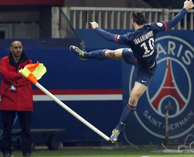 Paris St Germain's Zlatan Ibrahimovic,right, jumps and kicks a corner flag as he celebrates scoring.