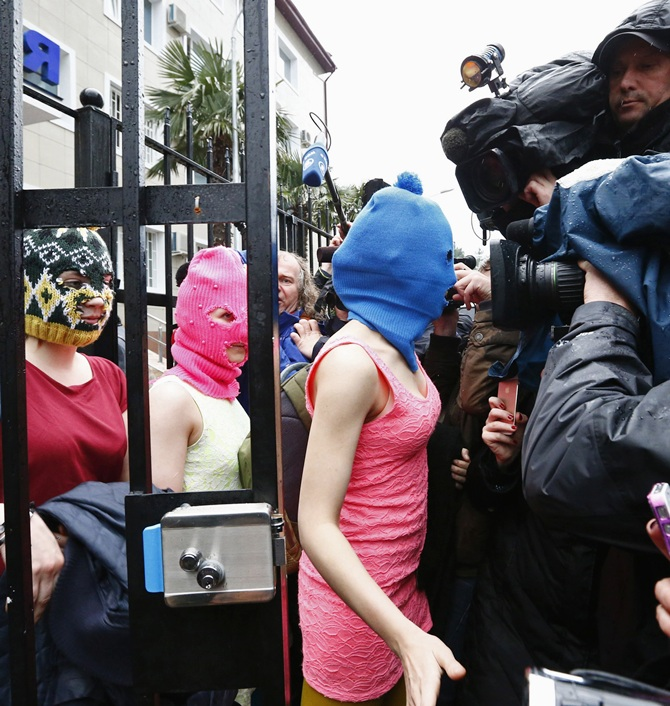 Masked members of Pussy Riot leave a police station in Adler during the 2014 Sochi Winter Olympics.