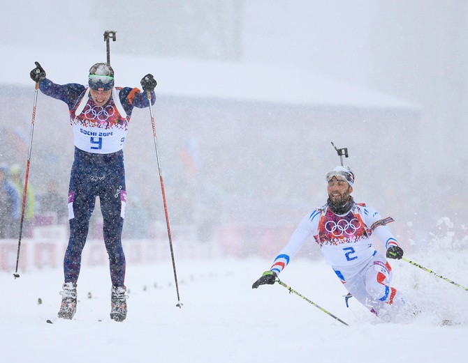 Martin Fourcade of France stretches for the finish line next to Emil Hegle Svendsen of Norway.