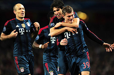 Toni Kroos of Bayern Munich celebrates scoring the opening goal with teammates Javi Martinez and Arjen Robben during the UEFA Champions League Round of 16 first leg match against Arsenal at Emirates Stadium in London on Wednesday