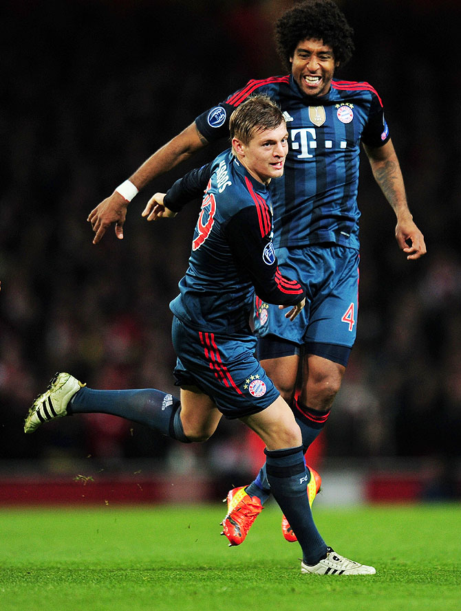 Toni Kroos of Bayern Muenchen celebrates scoring the opening goal with teammate Dante during their UEFA Champions League Round of 16 first leg match against Arsenal at Emirates Stadium in London on Wednesday