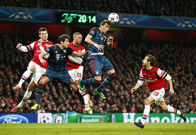 Bayern Munich's Mario Mandzukic (2nd from) and Javi Martinez (2nd from left) vie for the ball in an aerial challenge against Arsenal's Laurent Koscielny (left), Kieran Gibbs (centre) and Mathieu Flamini (right)