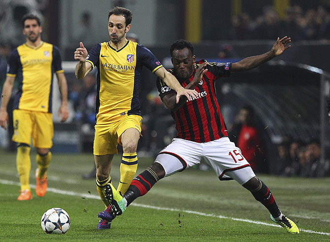 Juanfran of Atletico Madrid is challenged by Michael Essien of AC Milan during their Champions League match on Wednesday