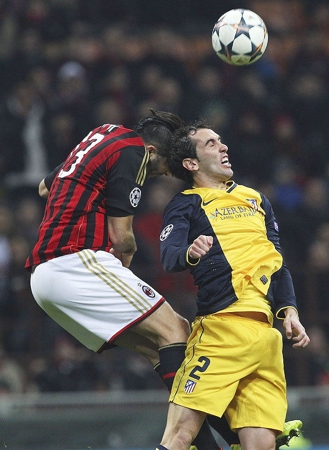 Diego Godin (right) of Atletico Madrid competes for the ball with Adil Rami (left) of AC Milan on Wednesday