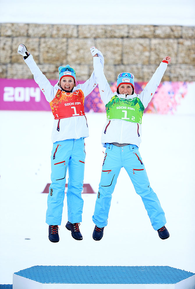 Gold medalists Marit Bjoergen (right) of Norway and teammate Ingvild Flugstad Oestberg celebrate during the flower ceremony for the Women's Team Sprint Classic Final on Wednesday