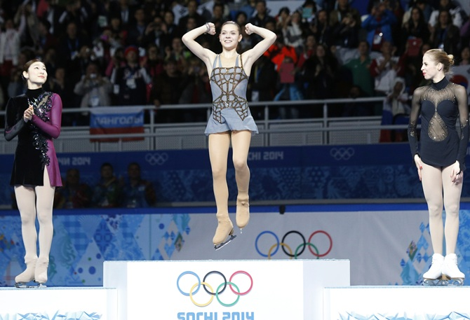 From left, Russia's Adelina Sotnikova celebrates in first place, Korea's Yuna Kim stands in second place and Italy's Carolina Kostner stands in third place on the podium.