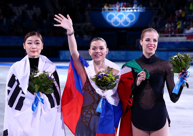 From Left, Silver medalist Yuna Kim of South Korea, gold medalist Adelina Sotnikova of Russia and bronze medalist   Carolina Kostner of Italy celebrate during the flower ceremony for the Ladies' Figure Skating.
