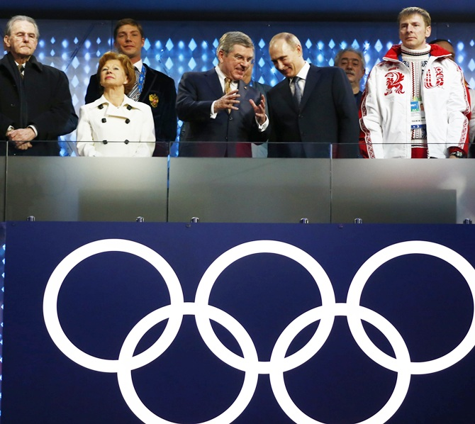 Russia's President Vladimir Putin talks with International Olympic Committee (IOC) President Thomas Bach, as Former President of the International Olympic Committee Jacques Rogge looks on, left, at the start of the closing ceremony.