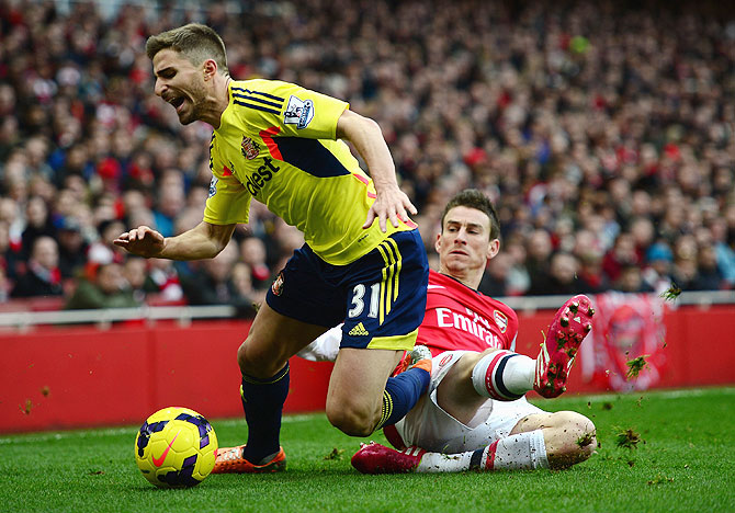 Fabio Borini of Sunderland is tackled by Laurent Koscielny of Arsenal during their English  Premier League match at Emirates Stadium on Saturday