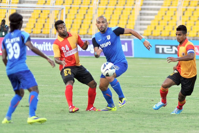Dempo's Beto, centre, dribbles past East Bengal defenders