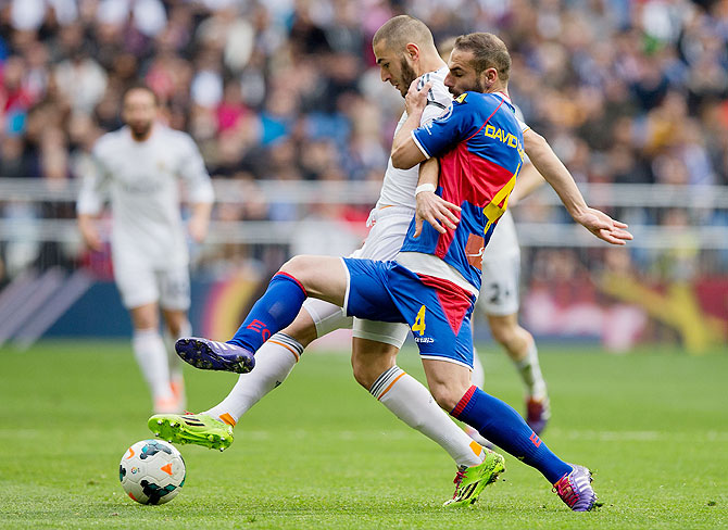 Karim Benzema of Real Madrid CF (left) competes for the ball with David Rodriguez Lomban of Elche FC during their La Liga match on Saturday