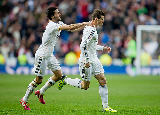 Real Madrid's Gareth Bale (right) celebrates with teammate Alvaro Arbeloa after scoring against Elche CF during their La Liga match at Estadio Santiago Bernabeu on Saturday