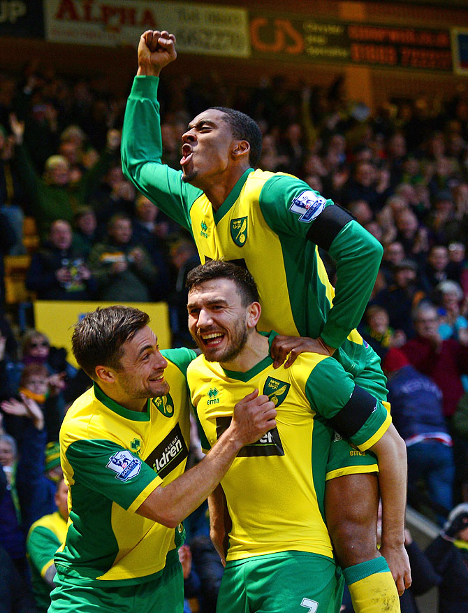 Robert Snodgrass of Norwich City (centre) celebrates with teammates Leroy Fer and Russell Martin after scoring the opening goal against Tottenham Hotspur at Carrow Road in Norwich on Sunday