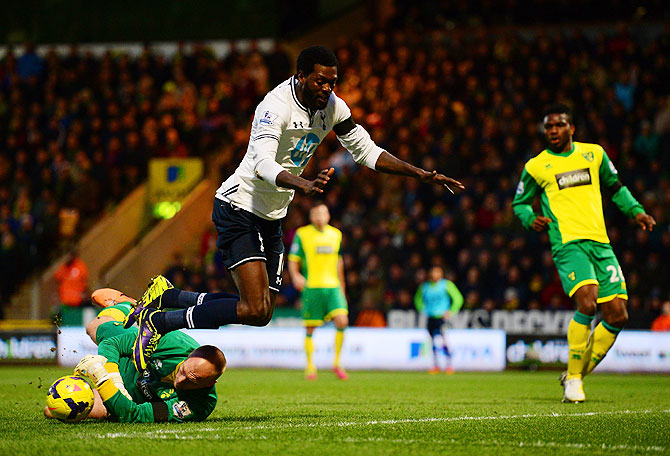 John Ruddy of Norwich City clashes with Emmanuel Adebayor of Tottenham Hotspur during their match on Sunday