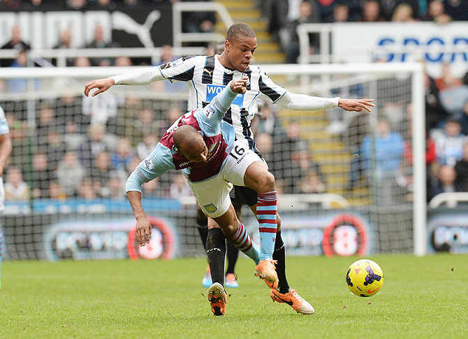 Loic Remy of Newcastle United tackles Fabian Delph of Aston Villa during their Premier League match at St James' Park in Newcastle on Sunday