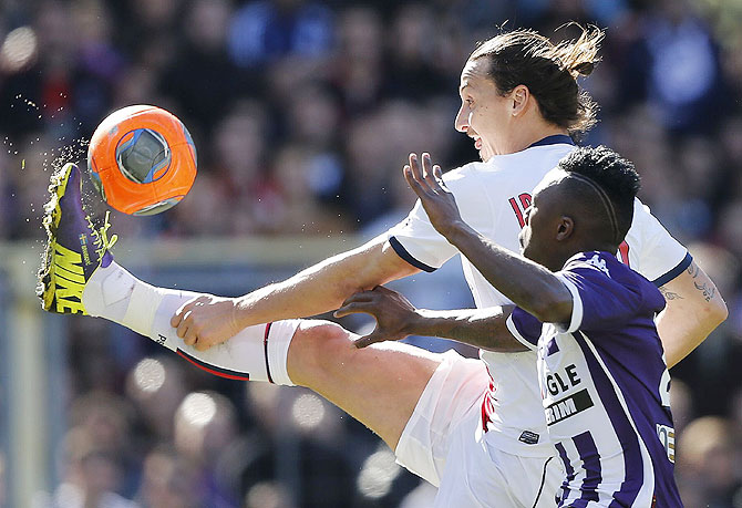 Paris St Germain's Zlatan Ibrahimovic challenges Toulouse's Steev Yago (right) during their French Ligue 1 match at the stadium in Toulouse