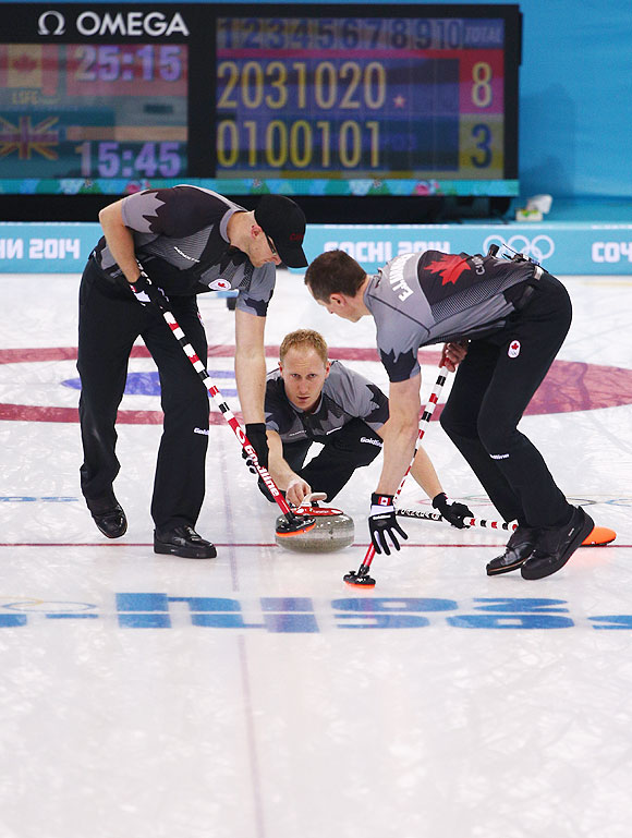 Brad Jacobs (centre) of Canada plays the final stone during the Men's Gold Medal match between Canada and Great Britain