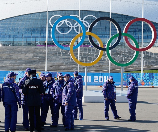 Security personnel walk past the Olympic Rings ahead of the Sochi 2014 Winter Olympics at the Olympic Park.