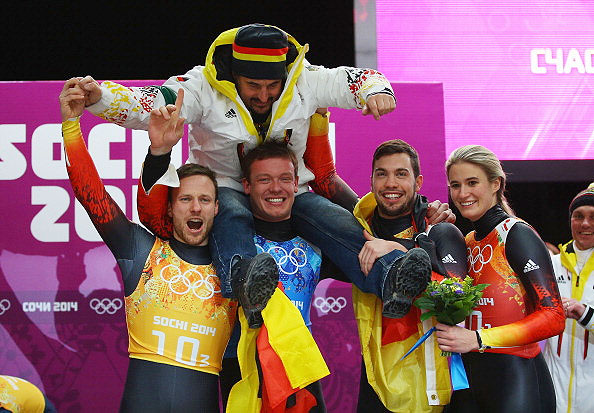 (From left) Gold medalists Tobias Arlt, Felix Loch, Tobias Wendl and Natalie Geisenberger of Germany lift   their coach Georg Hackl in celebration during the flower ceremony for the the Luge Relay at Sliding Center Sanki in Sochi on Thursday.