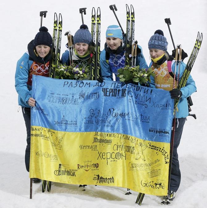 Gold medalists Vita Semerenko, Juliya Dzhyma, Olena Pidhrushna and Valj Semerenko of Ukraine celebrate after   the flower ceremony for the Biathlon Women's 4 x 6 km Relay.