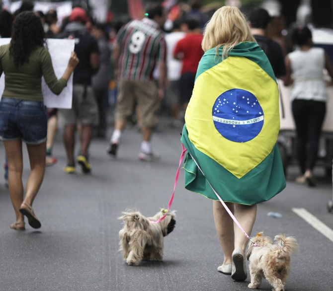 A woman walks her dogs during a protest on the streets near the Maracana stadium in Rio de Janeiro.