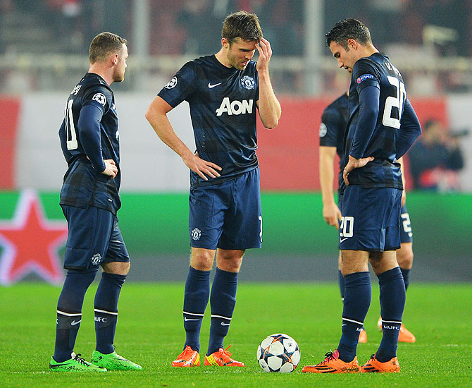 Wayne Rooney, Michael Carrick and Robin van Persie of Manchester United react as they restart the game after conceding the first goal during their Champions League Round of 16 first leg match against Olympiacos FC at Karaiskakis Stadium in Piraeus, Greece, on Tuesday