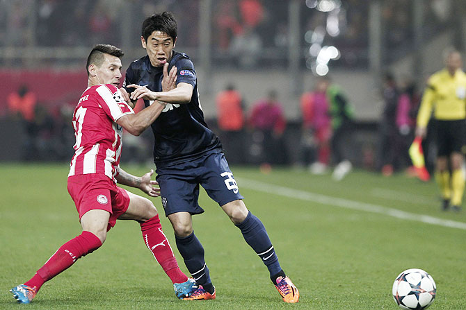 Olympiakos' Hernan Perez (left) challenges Manchester United's Shinji Kagawa during their Champions League match on Tuesday