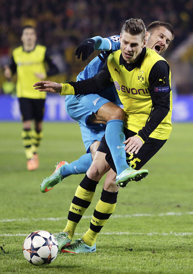 Zenit St Petersburg's Viktor Fayzulin and Borussia Dortmund's Lukasz Piszczek (right) get into a tangle as they fight for the ball during their Champions League match on Tuesday