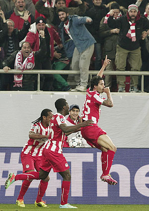 Olympiakos's Alejandro Dominguez (right) celebrates with his teammates after scoring a goal against Manchester United during their Champions League round of 16 first leg match at Karaiskaki stadium in Piraeus, near Athens, on Tuesday