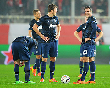 Wayne Rooney, Michael Carrick and Robin van Persie of Manchester United react as they restart the game after conceding the first goal during their UEFA Champions League Round of 16 first leg match against Olympiacos at Karaiskakis Stadium on Tuesday