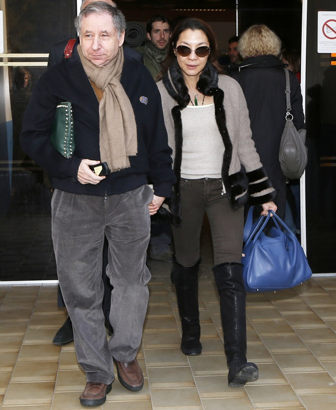 Former Ferrari team manager and current FIA President Jean Todt (left) and his girlfriend actress Michelle Yeoh leave the CHU hospital emergency unit in Grenoble, French Alps