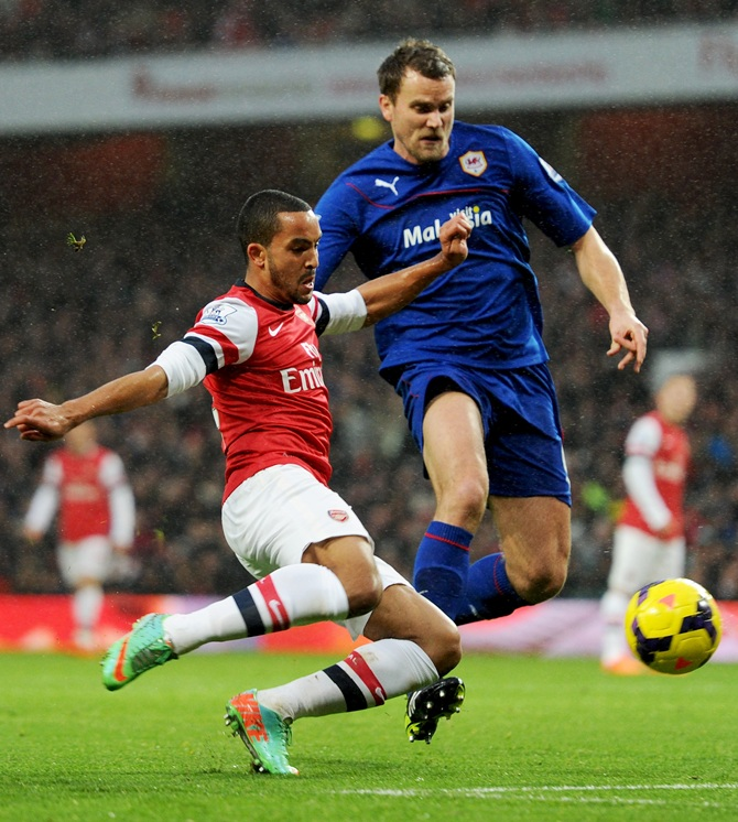 Theo Walcott of Arsenal battles with Ben Turner of Cardiff City