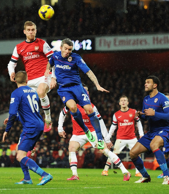 Per Mertesacker of Arsenal jumps with Kevin McNaughton of Cardiff City