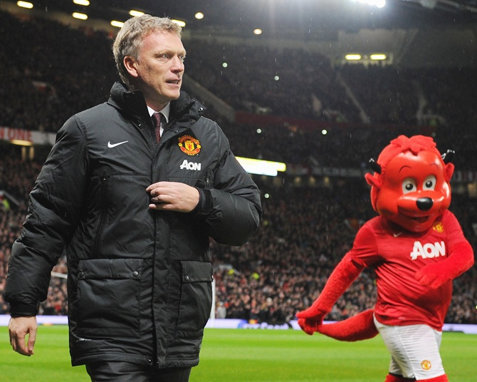 Manchester United Manager David Moyes walks with mascot Fred the Red