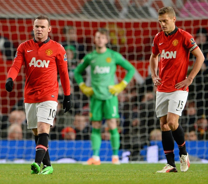 Wayne Rooney of Manchester United and his team-mate Nemanja Vidic (right) react after conceding a second goal