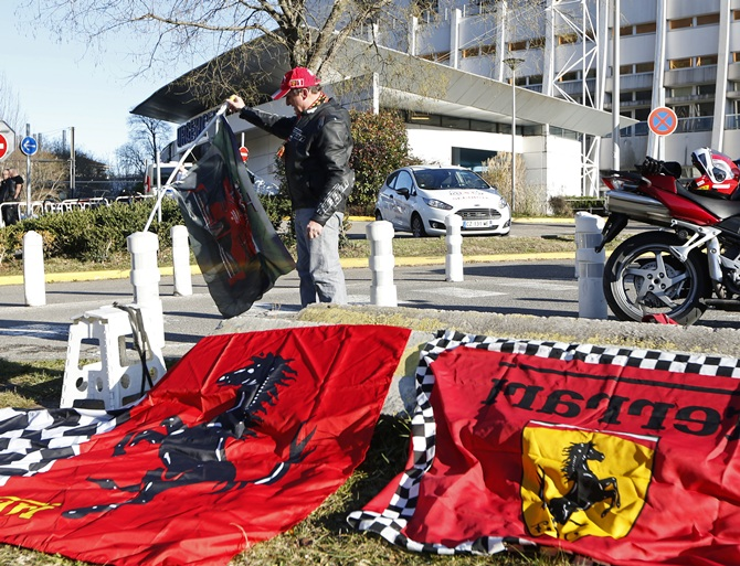 Dario, a Ferrari local fan, displays flags in front of the entrance of the emergency services at   the CHU Nord hospital in Grenoble, French Alps, where   retired seven-times Formula One world champion Michael Schumacher is hospitalized after a ski accident
