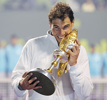 Rafael Nadal of Spain poses with his trophy after winning the Qatar Open final tennis match in Doha on Saturday