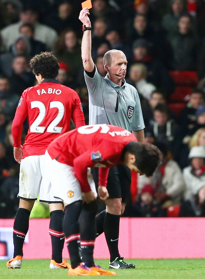 Referee Michael Dean shows a red card to Fabio of Manchester United