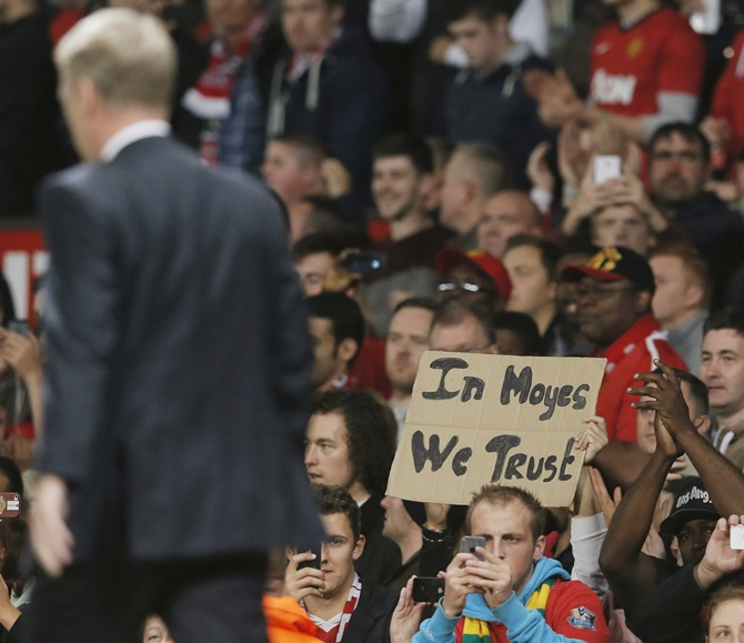 Manchester United's manager David Moyes walks to the dugout as a fan holds up a placard