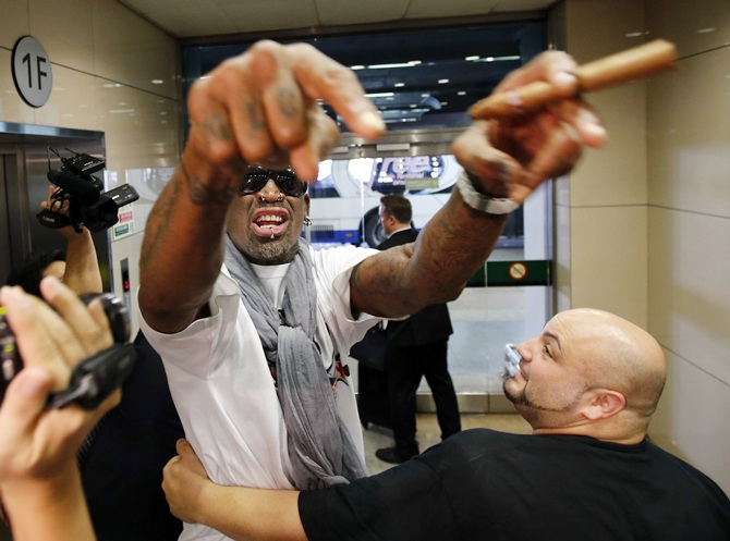 Former basketball star Dennis Rodman of the US gestures as he talks to journalists chasing him upon his arrival at Beijing