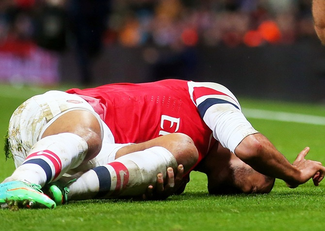 Theo Walcott of Arsenal lies injured on the pitch